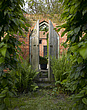 Brick wall,wooden gothic door and ferns in Garden, Lincolnshire - 12343-60-1