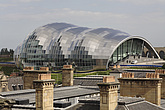 The Sage Gateshead (RIBA Inclusive Design Award) seen over rooftops with yellow and orange chimney stacks, Newcastle Upon Tyne, UK - 31876-100-1