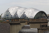The Sage Gateshead (RIBA Inclusive Design Award) seen over rooftops with yellow and orange chimney stacks, Newcastle Upon Tyne, UK - 31876-90-1