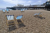 Deck chairs on the pebbly beach a with Brighton Pier in the distance, Brighton, Sussex - 12683-40-1