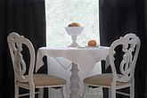 White pedestal table with cloth, fruit and bowl  with ornate dining chairs  in front of  opaque window - 12688-110-1