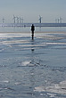 One of the 100 iron men at Crosby Beach as part of Anthony Gormley's Another Place, with wind generators behind, Liverpool, Merseyside, England - 12790-150-1