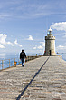 A man walks his dog to the lighthouse at the end of the Castle Breakwater in Guernsey, Channels Islands - 12880-80-1