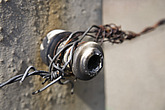 An insulating point where electrofied barbed wire is attached onto a concrete fence post at Auschwitz Concentration Camp in Poland, Eastern Europe - 12882-20-1