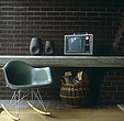 A glass-fibre Eames rocking chair stands infront of a concrete table against a dark brick wall - 60000-390-1