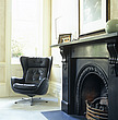 Black leather retro-style armchair and a large Victorian fireplace, London, England, UK, - 60418-10-1