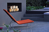 Detail of an orange sun-lounger on a patio beside an outdoor fireplace - 61071-20-1