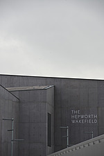 Closeup view of the front elevation and sign over the entrance of The Hepworth Wakefield with the edge of the pedestrian bridge over the River Calder... - 13298-50-1