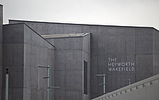 Closeup view of the front elevation and sign over the entrance of The Hepworth Wakefield with the edge of the pedestrian bridge over the River Calder... - 13298-80-1