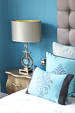 Gold bedside table against a aqua blue wall in British home - 14091-50-1