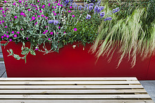 Red powder-coated steel planter with mixed planting of lychnis and grass with slatted wooden bench, designed by Modular - 14152-40-1