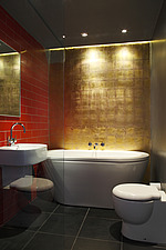 Dramatic bathroom with gold leaf wall behind bath, red wall tiles and black floor tiles - 14201-180-1