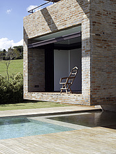 Chair on shaded terrace overlooking garden of Brazilian home - 14398-200-1
