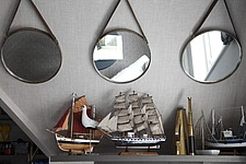 Model ships and other nautical paraphanalia on a shelf beneath 3 circular mirrors - 16126-150-1