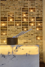 Backlit onyx-fronted counter, with behind, shelving on a bare brick wall carrying candles in frosted glass cups at the Da Yang architecture studio of... - 13325-120-1