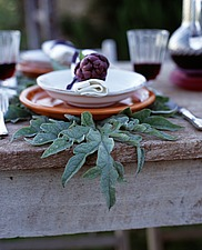 Rustic wooden table with globe artichoke in bowl and artichoke leaf - 16407-140-1