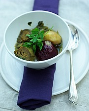 White bowl with cooked globe artichokes, spoon and purple serviette - 16407-30-1