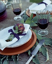 Purple globe artichoke on white serviette and orange plate on wooden table with large artichoke leaves and glasses of red wine - 16407-80-1