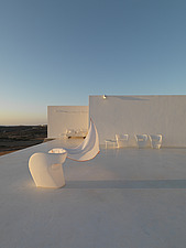 White chairs on white seating area overlooking sea - 16400-110-1