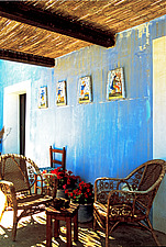 Shady straw-roofed verandah with blue walls and basket chairs - 16440-570-1