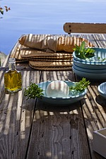 Al Fresco outdoor dining table by sea with blue plates, bread and olive oil - 16440-770-1