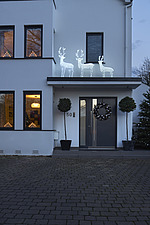 Exterior view of residential building with white and silver Christmas decorations, dusk - 16753-280-1