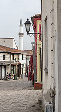 A view of the old town in Skopje, Macedonia, including shops, a lamp, cobblestone road, and a minaret - 16856-790