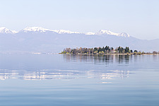 A small hotel on an isolated peninsula in Lake Ohrid, in Macedonia, with snow-capped Albanian mountains beyond - 16856-840