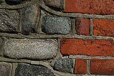Close up of a red clay brick and granite cobble wall with mortar - 10639-280-1