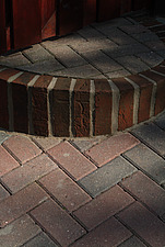 Close up of red clay herring bone pattern pavings with curved step edged by soldier course of bricks - 10639-460-1