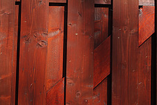Close up of a red stained elaborate timber fence panel - 10639-470-1