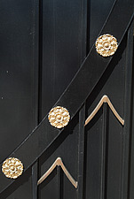 Backgrounds - detail of black stained wooden gate decorated with gold medallions and chevrons - 10639-530-1
