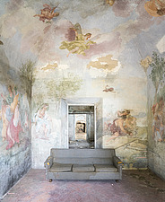 a beautiful fresco covering the whole room and a sofa in the middle of the room in an abandoned villa - ARC101296