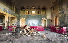 a room in an abandoned disco with a lamp on the floor and red sofas, in Italy - ARC101507