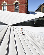 A boy climbs the steps of the new Sackler Courtyard at the V&A, London, UK, completed in 2017 - ARC104225
