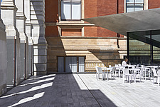 Visitors sit at the cafe enjoying the sun in the new Sackler Courtyard at the V&A, London, UK, completed in 2017 - ARC104228