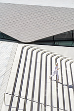 A women runs down the steps of the new Sackler Courtyard at the V&A, London, UK, completed in 2017 - ARC104230